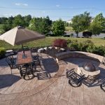 a stamped concrete patio with area for fire pit and an area for a dining table