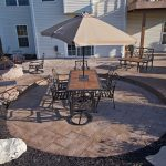 an area for a dining table sits on a stamped concrete patio