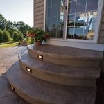 A set of decorative concrete steps leads to the house