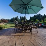 A dining table sits on a stamped concrete patio