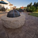 A fire pit on a stamped concrete patio